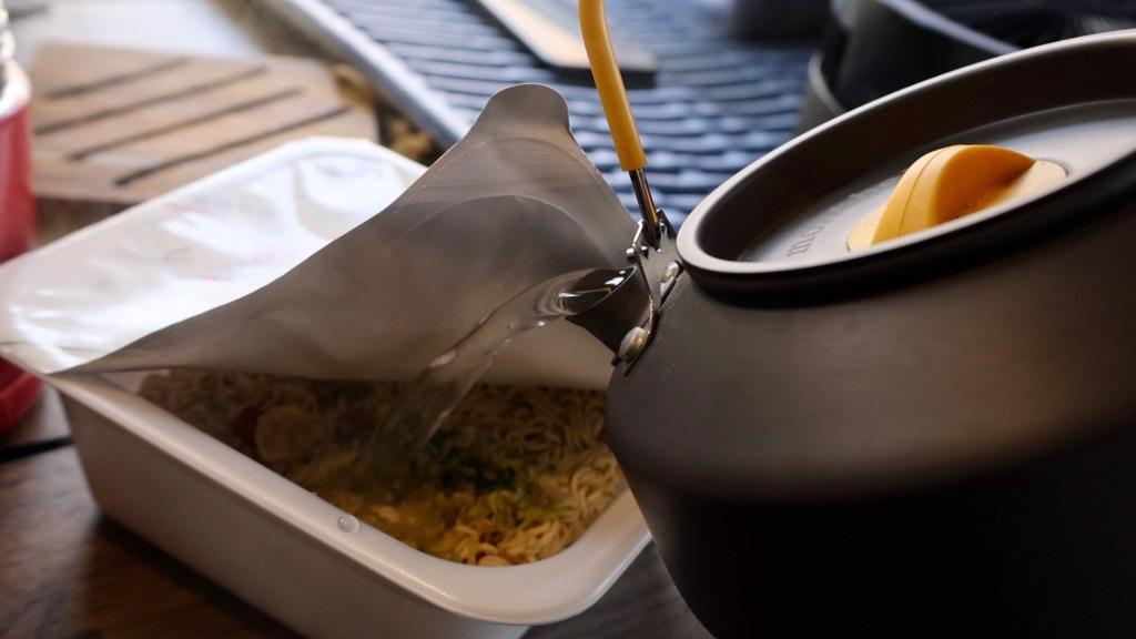 カップ焼きそばにやかんでお湯を注ぐ