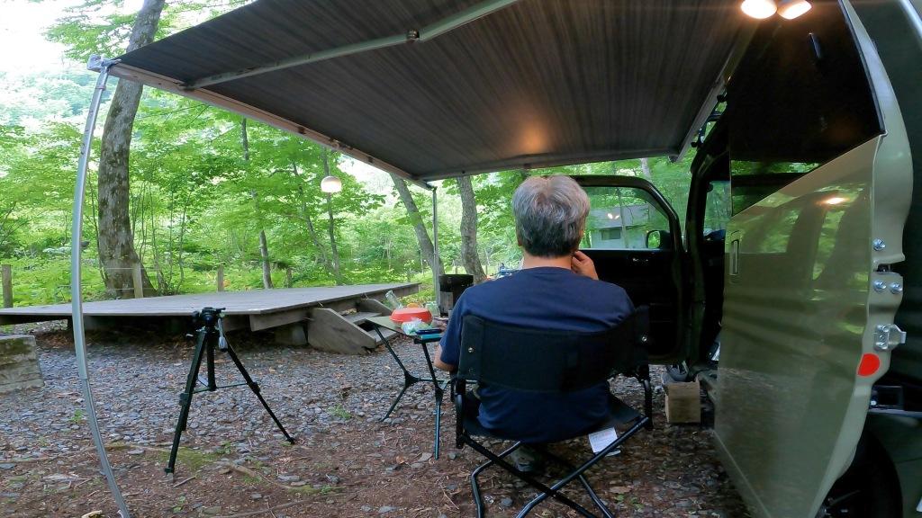 サイドオーニングの下でくつろぐキャンプ場の朝